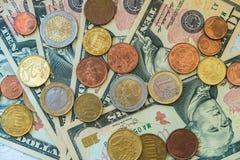 Moedas do Euro de denomina??es diferentes no fundo das notas de d?lar Close-up de diversas euro- moedas Conceito da troca no fotos de stock