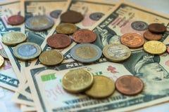 Moedas do Euro de denomina??es diferentes no fundo das notas de d?lar Close-up de diversas euro- moedas Conceito da troca no fotografia de stock