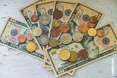 Moedas do Euro de denomina??es diferentes no fundo das notas de d?lar Close-up de diversas euro- moedas Conceito da troca no imagens de stock