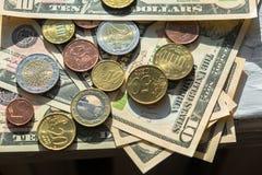 Moedas do Euro de denomina??es diferentes no fundo das notas de d?lar Close-up de diversas euro- moedas Conceito da troca no imagens de stock royalty free