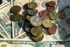 Moedas do Euro de denomina??es diferentes no fundo das notas de d?lar Close-up de diversas euro- moedas Conceito da troca no imagem de stock royalty free