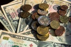 Moedas do Euro de denomina??es diferentes no fundo das notas de d?lar Close-up de diversas euro- moedas Conceito da troca no imagem de stock