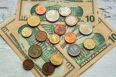 Moedas do Euro de denomina??es diferentes no fundo das notas de d?lar Close-up de diversas euro- moedas Conceito da troca no foto de stock