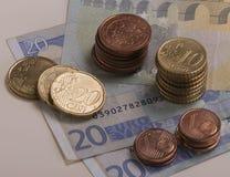 Moedas do Euro empilhadas em contas do Euro Foto de Stock Royalty Free