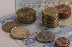 Moedas do Euro empilhadas em contas do Euro Foto de Stock