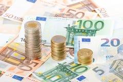 Moedas do Euro empilhadas no euro- fundo das cédulas Fotografia de Stock