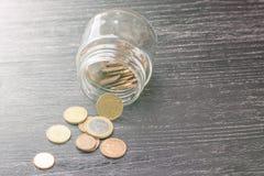 Moedas do Euro na baliza transparente em uma tabela de madeira preta foto de stock