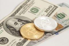 Moedas douradas e de prata do bitcoin e cem cédulas do dólar Fotos de Stock