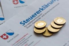 Moedas douradas no formulário suíço da declaração de imposto, cantão de Zurique foto de stock