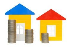 Moedas e casas imagem de stock