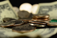 Moedas e dólares dos E.U. em um dólar do primeiro plano do foco seletivo da pilha Fotos de Stock Royalty Free