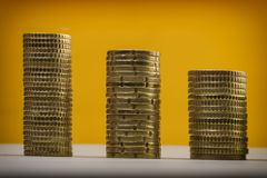 Moedas e eurocents do Euro empilhados em um fundo amarelo Euro m Fotografia de Stock Royalty Free