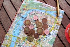 Moedas e mapa Fotografia de Stock Royalty Free
