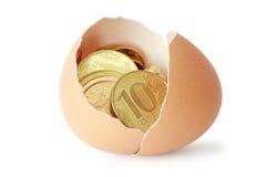 Moedas em casca de ovo quebrada Fotografia de Stock