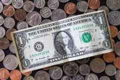 Moedas empilhadas dos E.U. cercadas por moedas e por rolos do papel Fotos de Stock Royalty Free