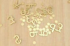 Moedas empilhadas e símbolo da moeda na tabela Fotografia de Stock