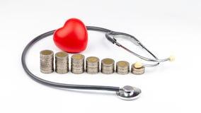Moedas, estetoscópio e coração vermelho, dinheiro de salvamento para despesas médicas e conceito dos cuidados médicos fotos de stock royalty free