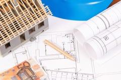 Moedas euro-, diagramas bondes, acessórios para trabalhos do coordenador e casa sob a construção, conceito home de construção do  Fotografia de Stock Royalty Free