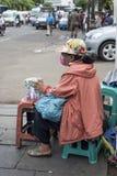 Moedas indonésias das trocas da mulher em uma rua de Jakarta perto da estação de Kota fotografia de stock
