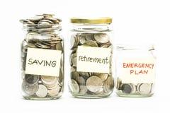 Moedas isoladas no frasco com etiqueta da economia, da aposentadoria e do plano de emergência Foto de Stock Royalty Free