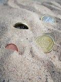 Moedas na areia Fotografia de Stock Royalty Free