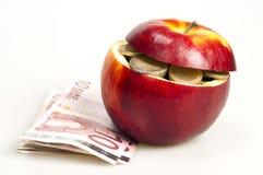 Moedas na maçã Fotografia de Stock Royalty Free