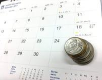 Moedas no calendário Fotografia de Stock