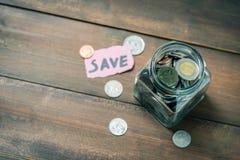 Moedas no frasco de vidro, conceito de salvamento do dinheiro fotografia de stock royalty free