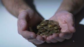 Moedas que caem nas mãos colocadas vazias da pessoa, salário pequeno para trabalho baixo-pago video estoque