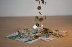 Moedas que caem no dinheiro fotografia de stock