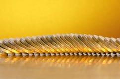 Moedas que encontram-se na superfície dourada com um fundo dourado Fotografia de Stock Royalty Free