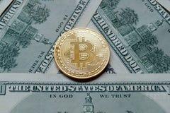 Moedas simbólicas do bitcoin em cédulas de cem dólares Fotografia de Stock Royalty Free