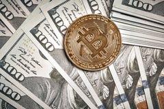 Moedas simbólicas do bitcoin em cédulas de cem dólares Dinheiro do bitcoin da troca para um dólar Foto de Stock