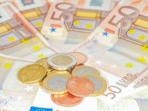 Moedas sobre 50 contas do Euro Foto de Stock