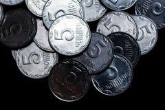 Moedas ucranianas isoladas no fundo preto Opinião do Close-up As moedas são ficadas situadas acima do centro do quadro foto de stock royalty free