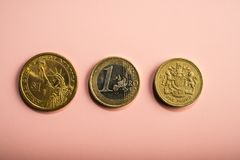 Moedas um dólar, um euro, uma libra em um fundo cor-de-rosa Fotografia de Stock Royalty Free