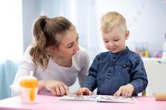 Moeder of babysitter die een boek lezen aan jong geitje binnen royalty-vrije stock foto