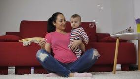 Moeder blazende zeepbels met baby thuis stock video