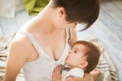Moeder de borst gevende baby in haar wapens thuis Mammaborst die - haar pasgeboren kind voeden Baby die moeder` s melk eten Conce stock afbeelding