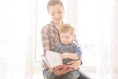 Moeder die aan haar kind een interessant verhaal lezen stock afbeeldingen