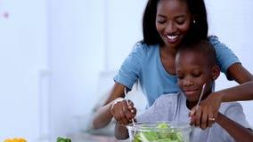 Moeder die aan haar zoon onderwijzen hoe te salade te mengen stock footage