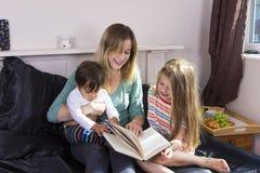 Moeder die aan jonge geitjes in bed lezen stock foto's