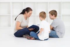 Moeder die aan kinderen leest Royalty-vrije Stock Afbeeldingen