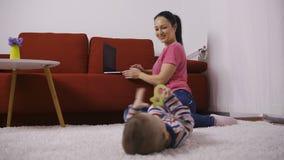 Moeder die aan laptop dichtbij babyzoon thuis werken stock video