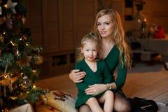 Moeder die aanbiddelijke mollig binnen houden weinig meisje van het blondemeisje stock foto