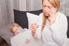 Moeder die arts roepen en thermometer bekijken Stock Foto's