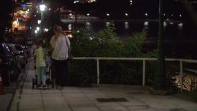 Moeder die avondgang met oudere zoon en baby hebben stock footage