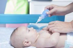 Moeder die baby neusaspirator met behulp van Royalty-vrije Stock Foto's