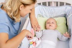 Moeder die baby in voederbak bekijken stock afbeeldingen