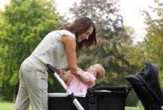 Moeder die baby zetten in kinderwagen Royalty-vrije Stock Afbeelding